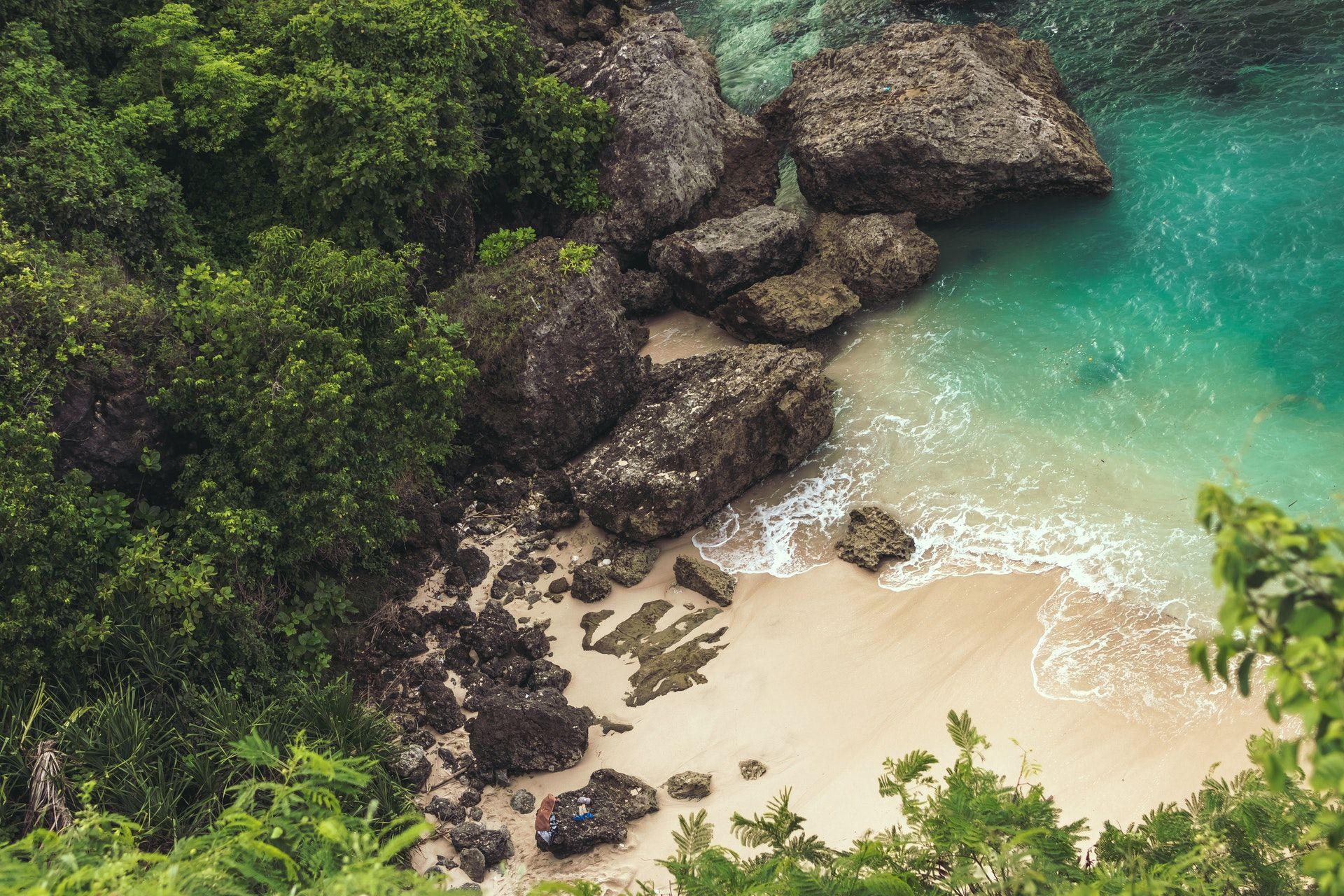 عکس زمینه نمای هوایی از ساحل نزدیک سنگ خاکستری بزرگ پس زمینه