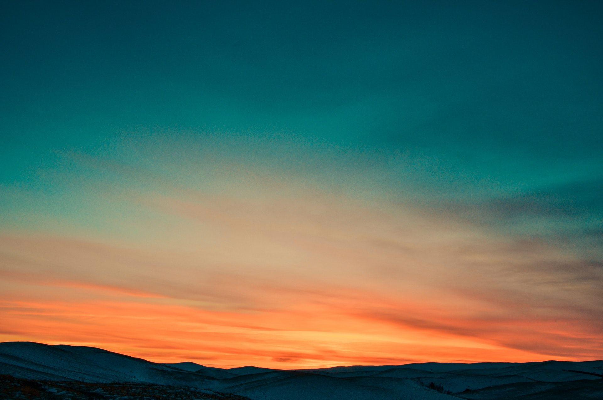 عکس زمینه غروب خورشید پشت کوه های پوشیده از برف پس زمینه