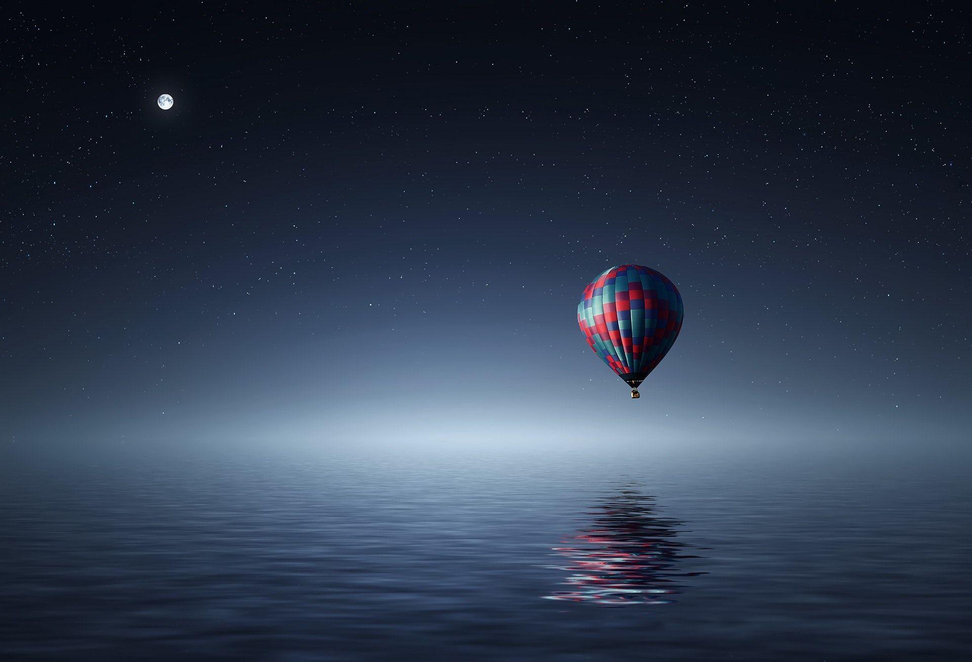 عکس زمینه بالون شناور در هوا روی آب در شب پس زمینه