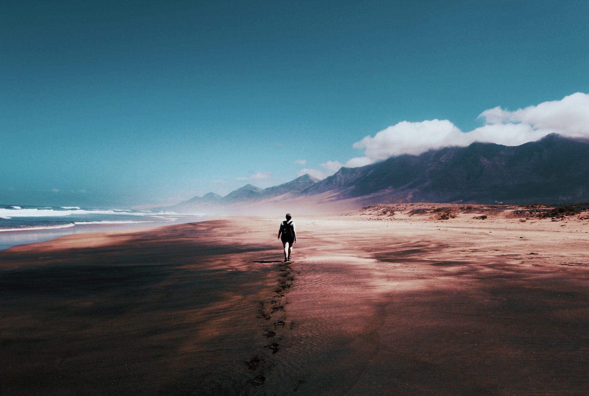 عکس زمینه فرد در حال راه رفتن بر روی جزیره متروک پس زمینه