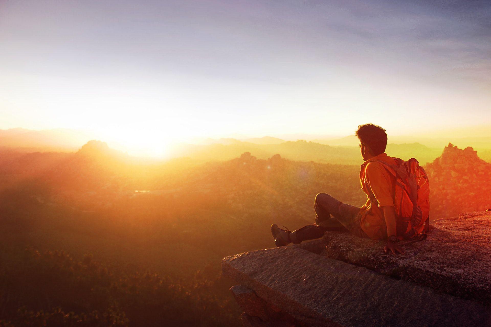 عکس زمینه مرد نشسته در لبه روبرو غروب پس زمینه