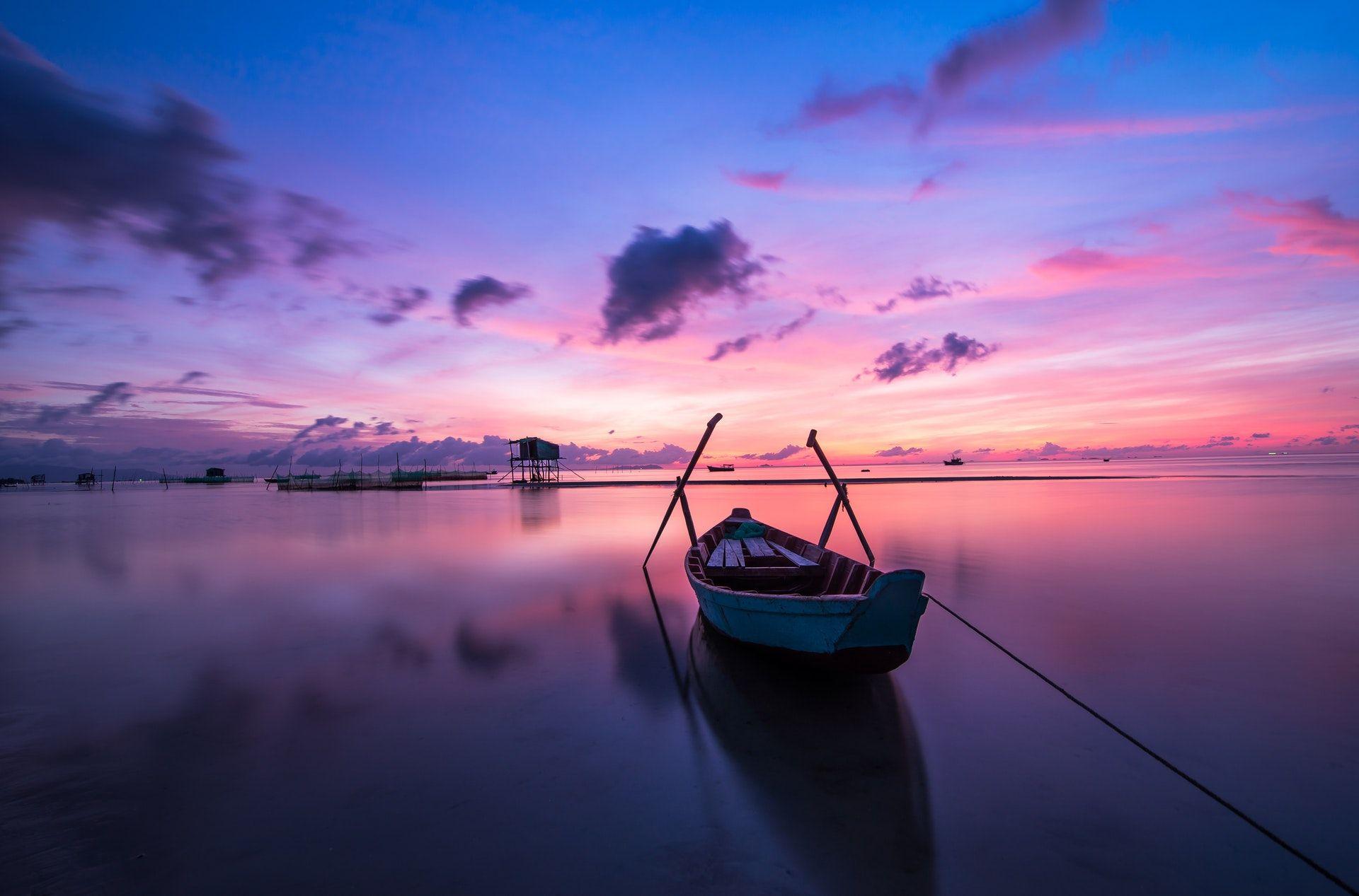 عکس زمینه قایق کوچک در آب هنگام طلوع پس زمینه