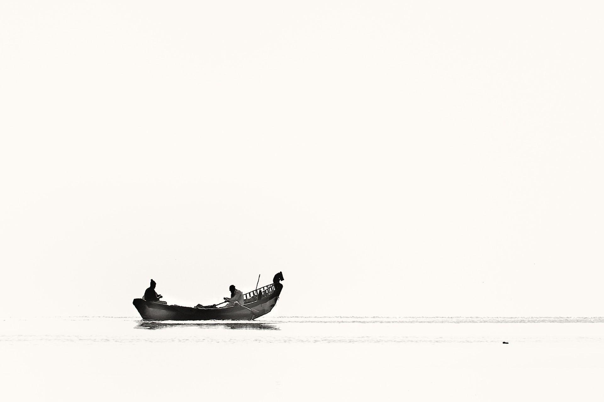 عکس زمینه دو فرد قایق سوار در آب پس زمینه