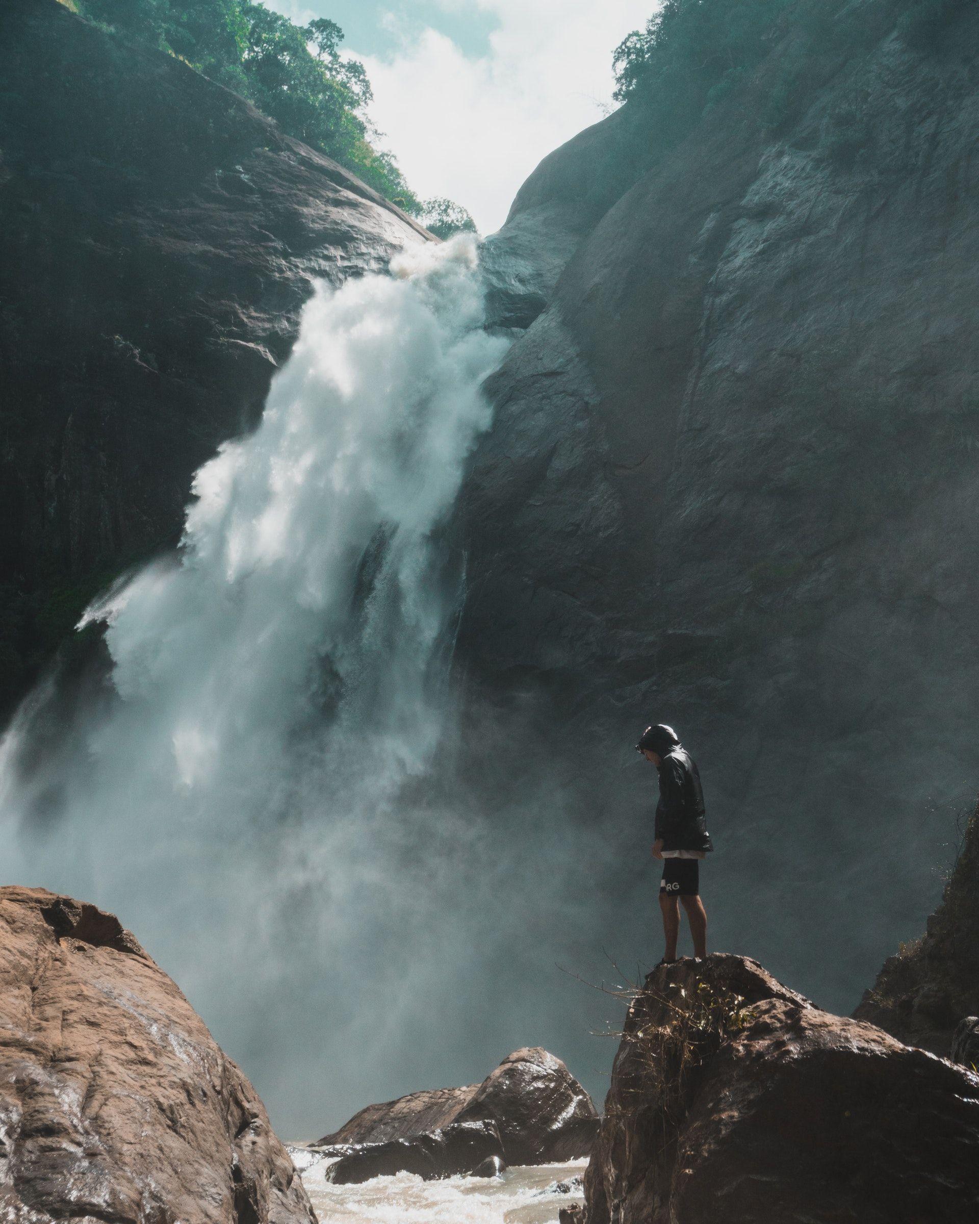 عکس زمینه مرد ایستاده کنار آبشار پس زمینه