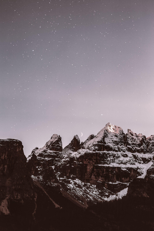 عکس زمینه کوه های پوشیده از برف در شب پس زمینه