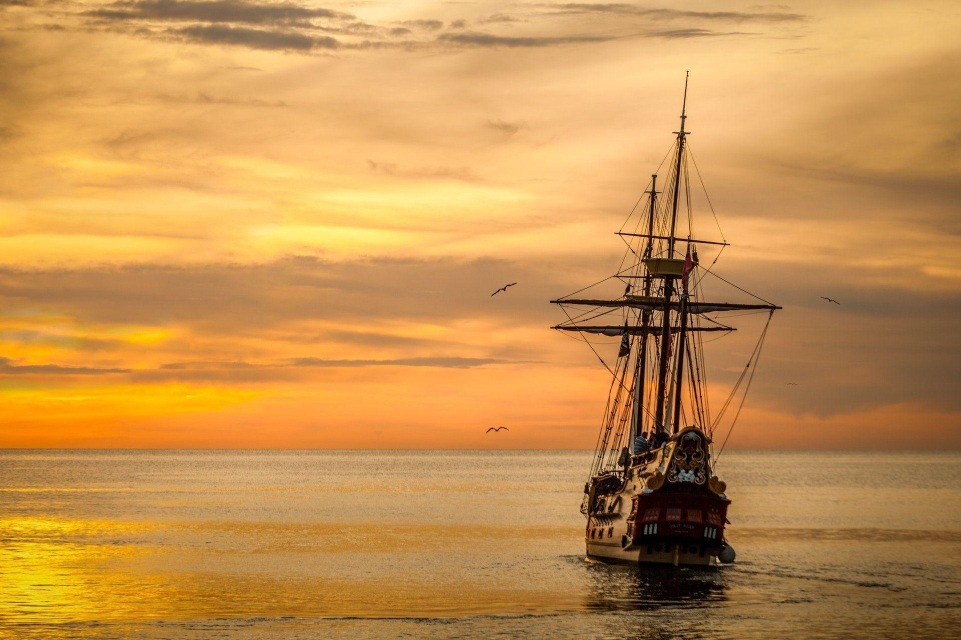 عکس زمینه قایق در غروب دریا پس زمینه
