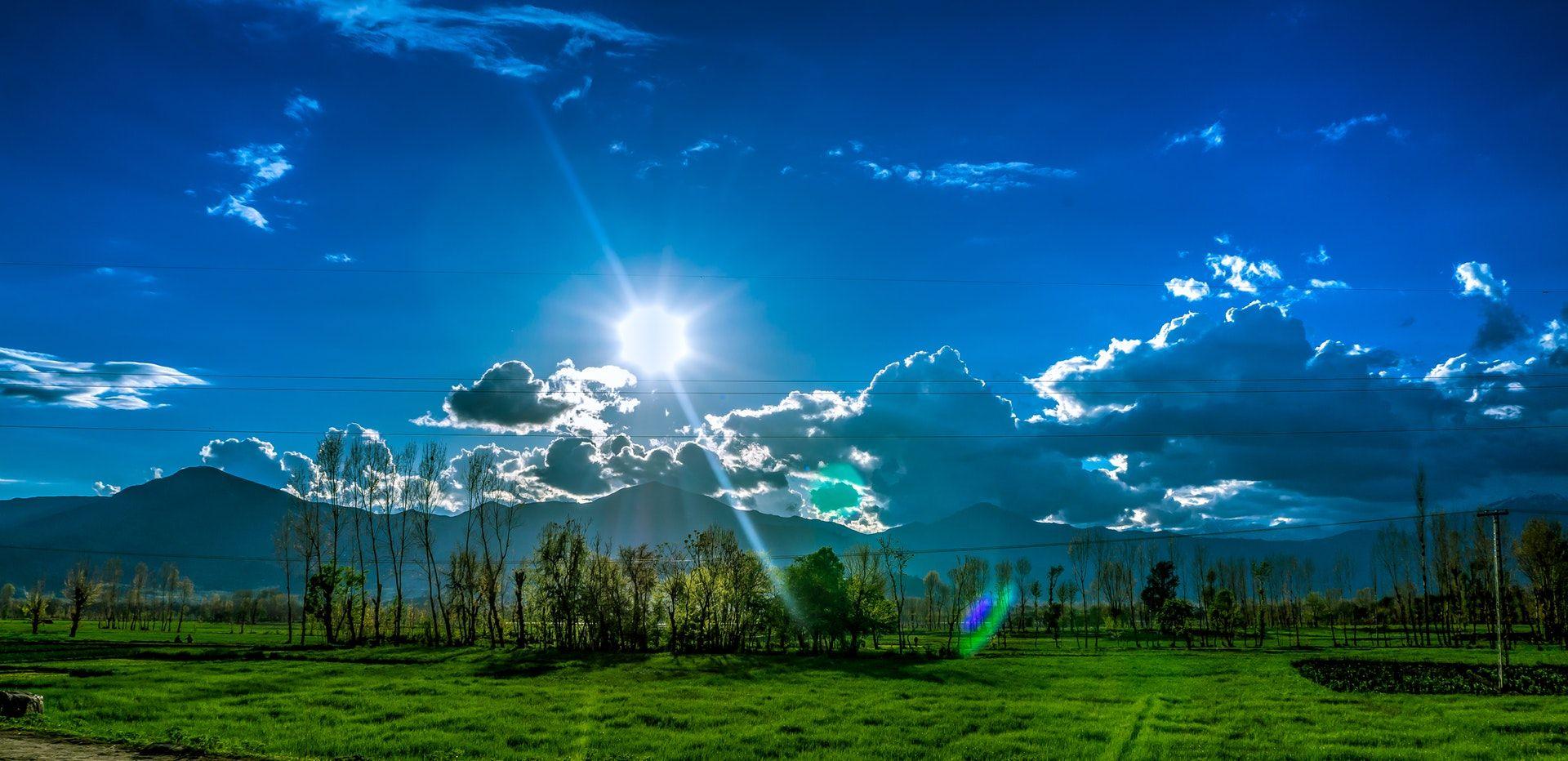 عکس زمینه آسمان نیمه ابری و دشت سر سبز پس زمینه