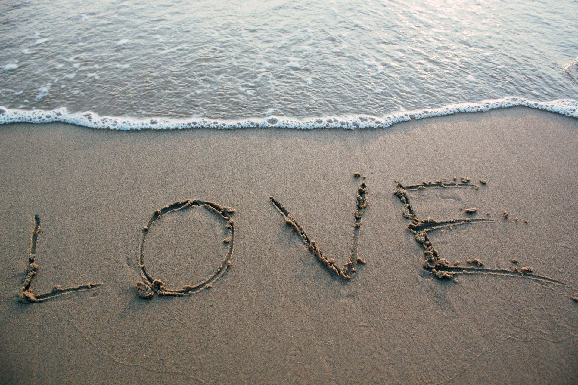 عکس زمینه متن عشق بر روی ساحل دریا پس زمینه