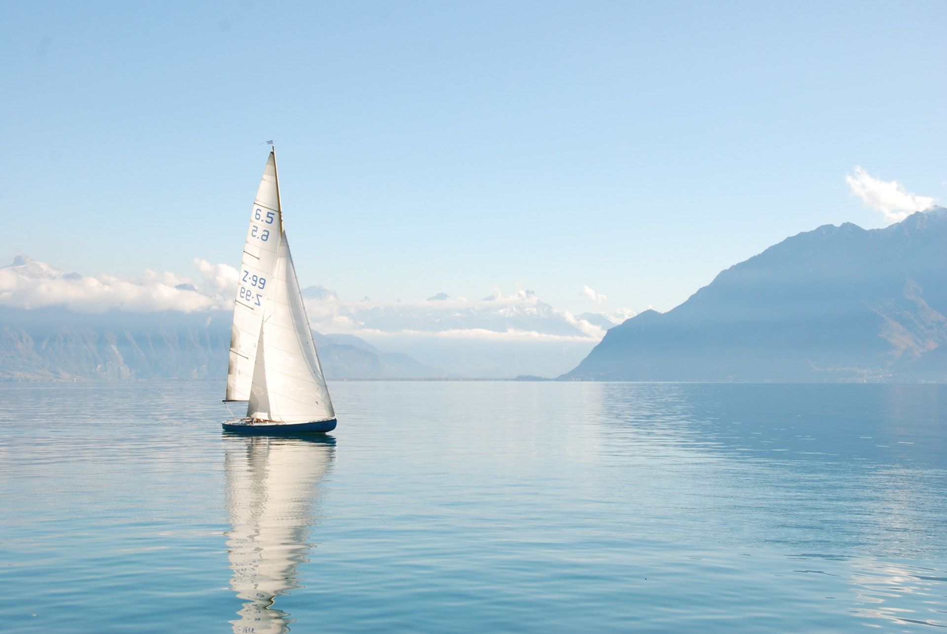 عکس زمینه قایق بادبانی سفید در آب پس زمینه