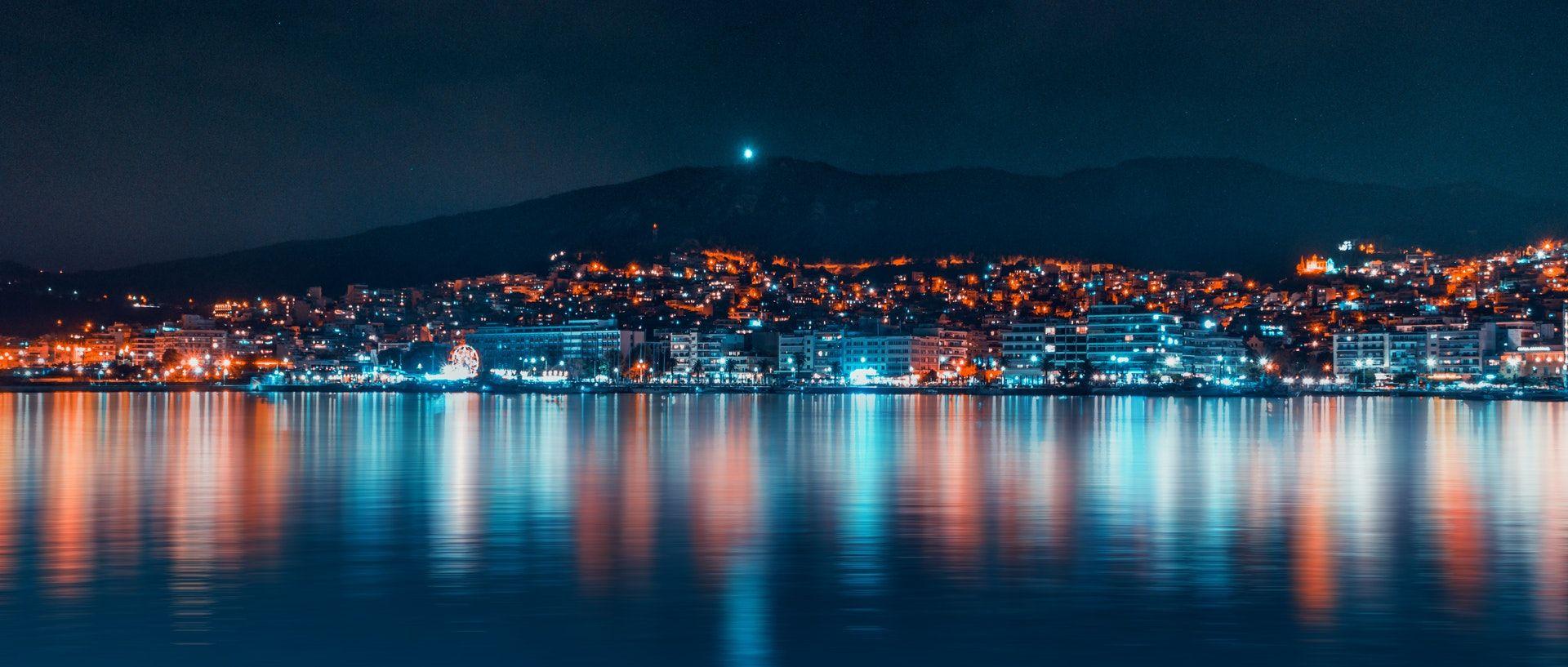 عکس زمینه ساختمان های شهر در نزدیکی آب در شب پس زمینه