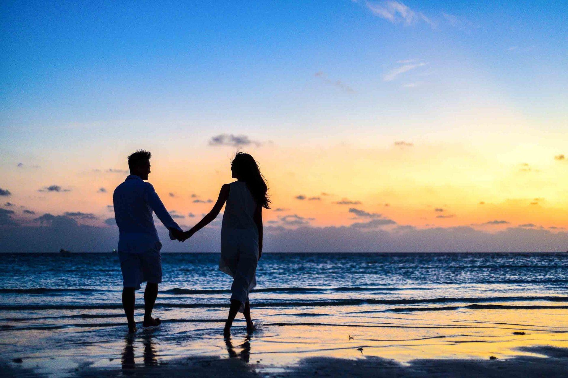 عکس زمینه زن و مرد در ساحل دریا هنگام طلوع پس زمینه