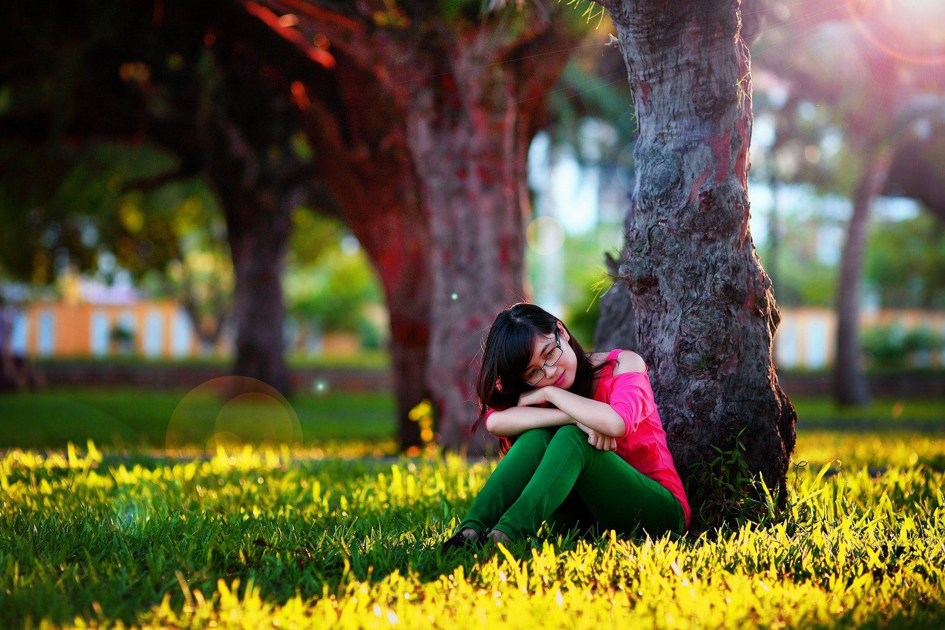 عکس زمینه دختر نشسته در کنار درخت پس زمینه