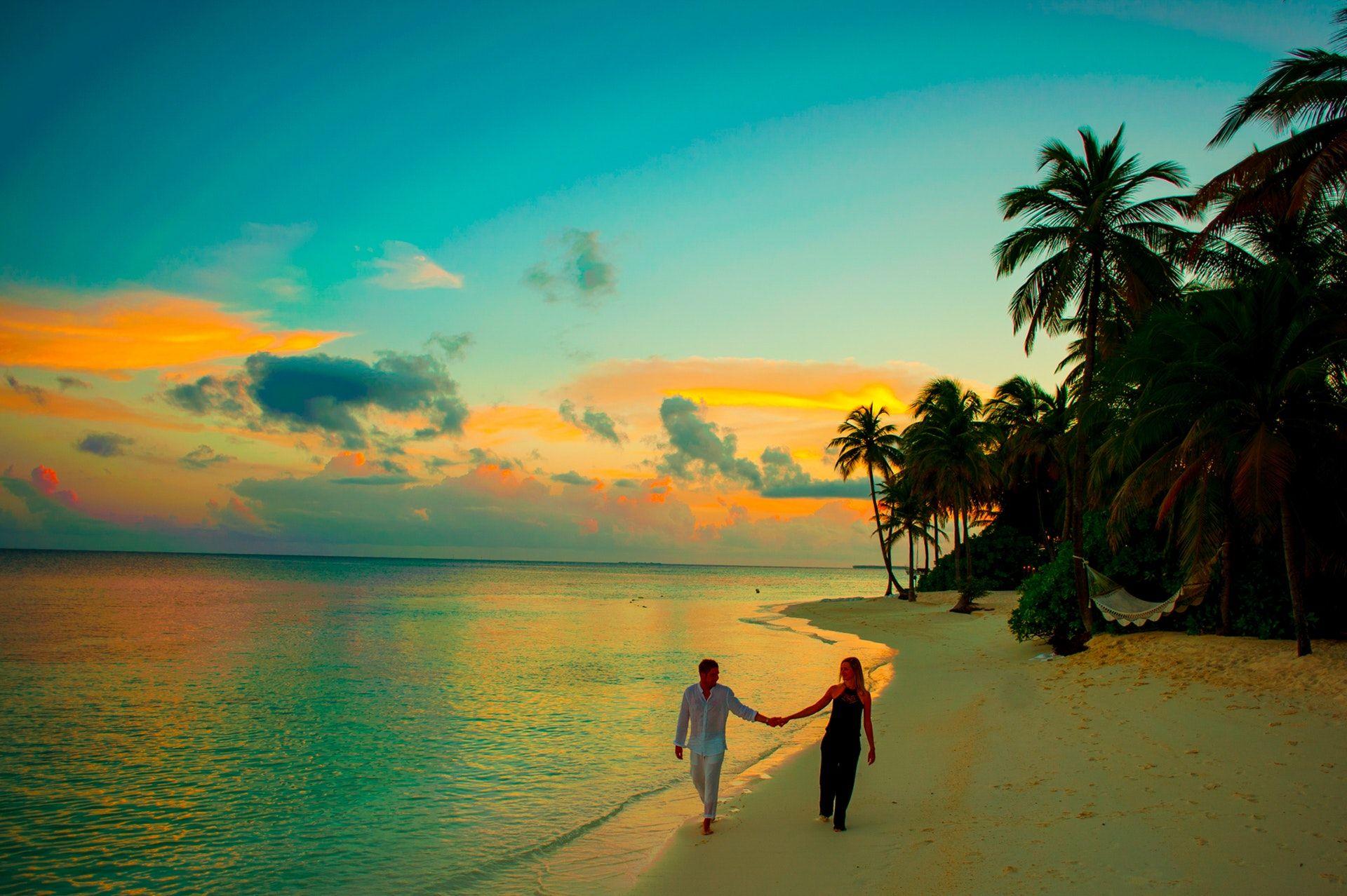 عکس زمینه زن و مرد در غروب ساحل پس زمینه