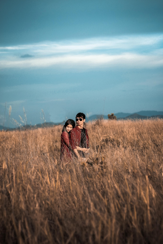 عکس زمینه پسر و دختر در علف زار پس زمینه