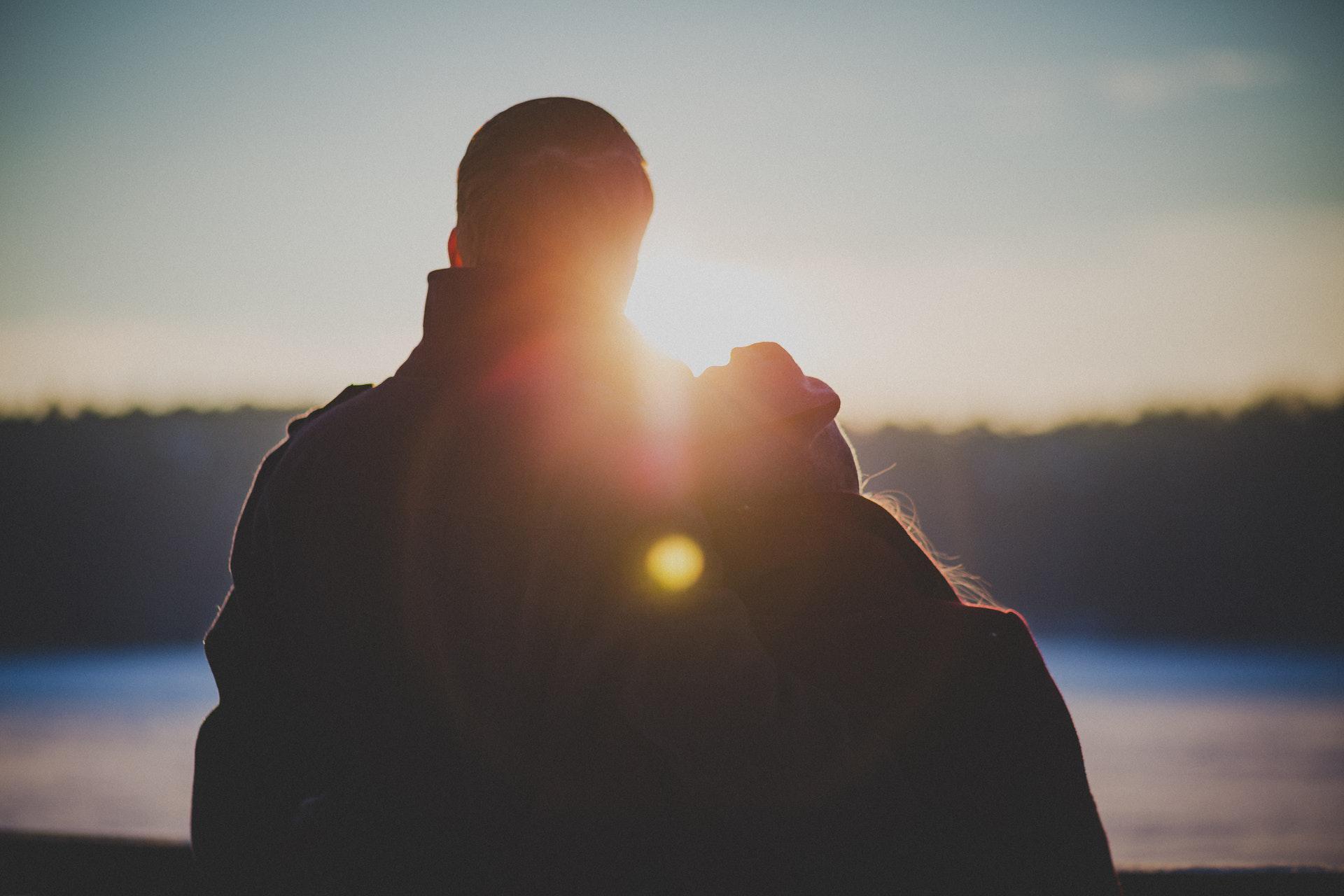 عکس زمینه پسر و دختر ایستاده در امتداد نور پس زمینه