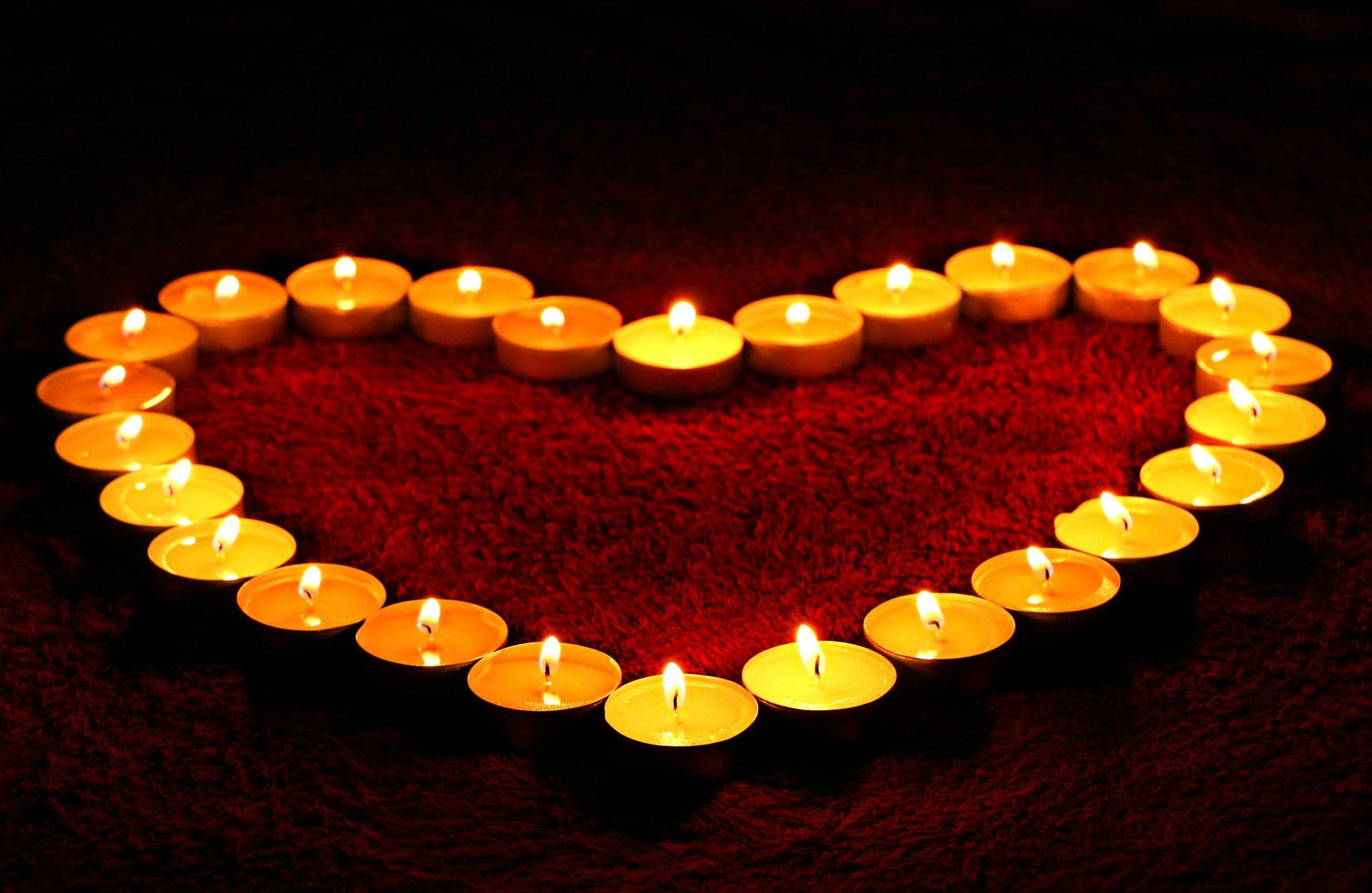 عکس زمینه شمع های روشن به شکل قلب پس زمینه