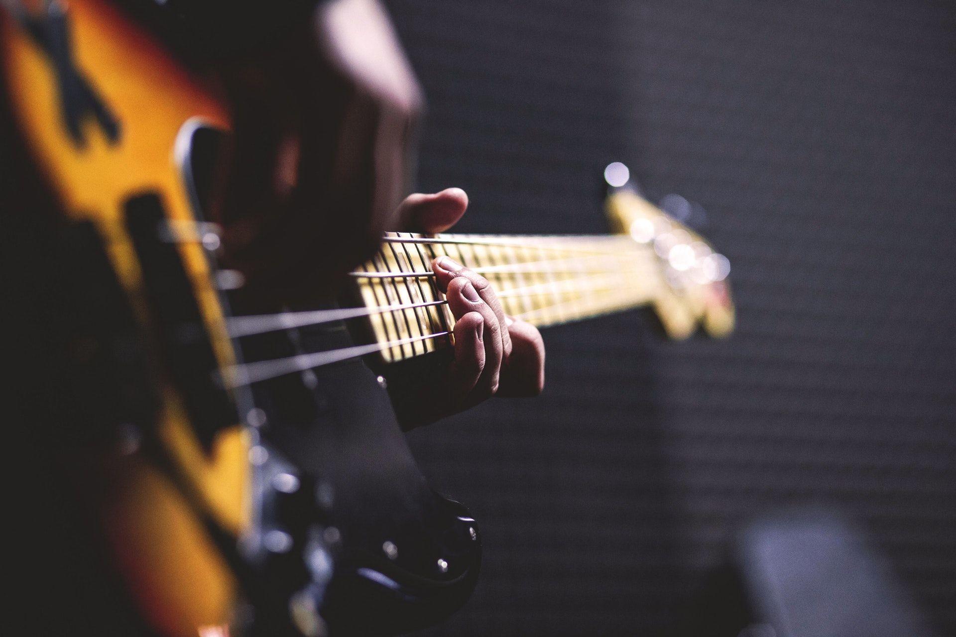عکس زمینه گیتار الکتریک و نوازنده پس زمینه