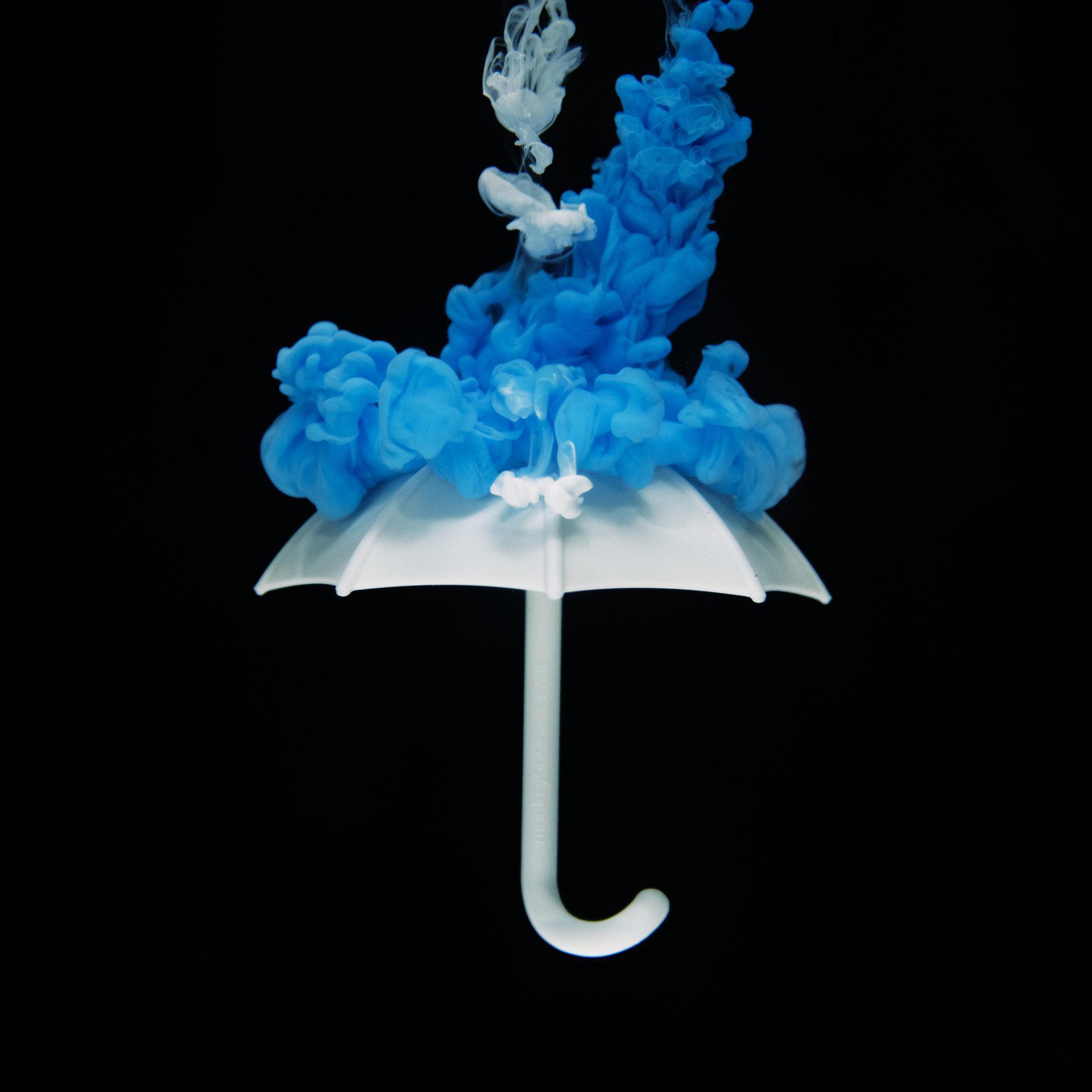 عکس زمینه چتر سفید با دود آبی با پس زمینه سیاه پس زمینه
