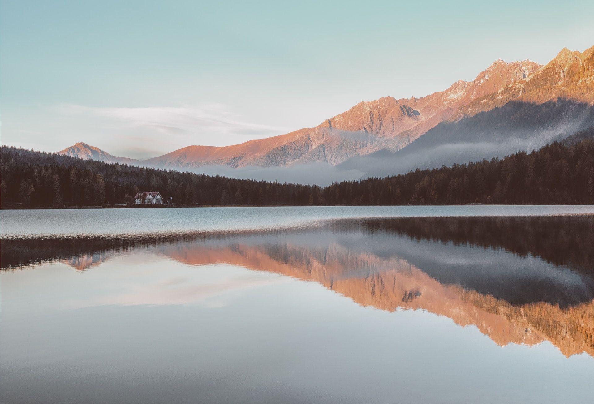 عکس زمینه رفلکس کوه در آب دریاچه پس زمینه