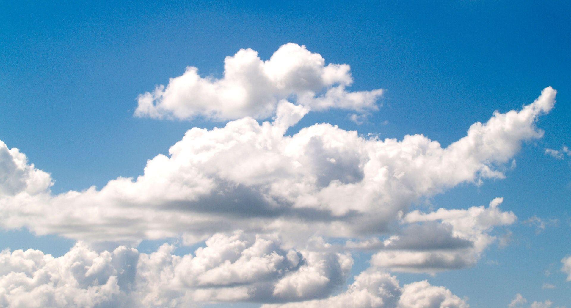 عکس زمینه ابرهای سفید در آسمان آبی آفتابی پس زمینه