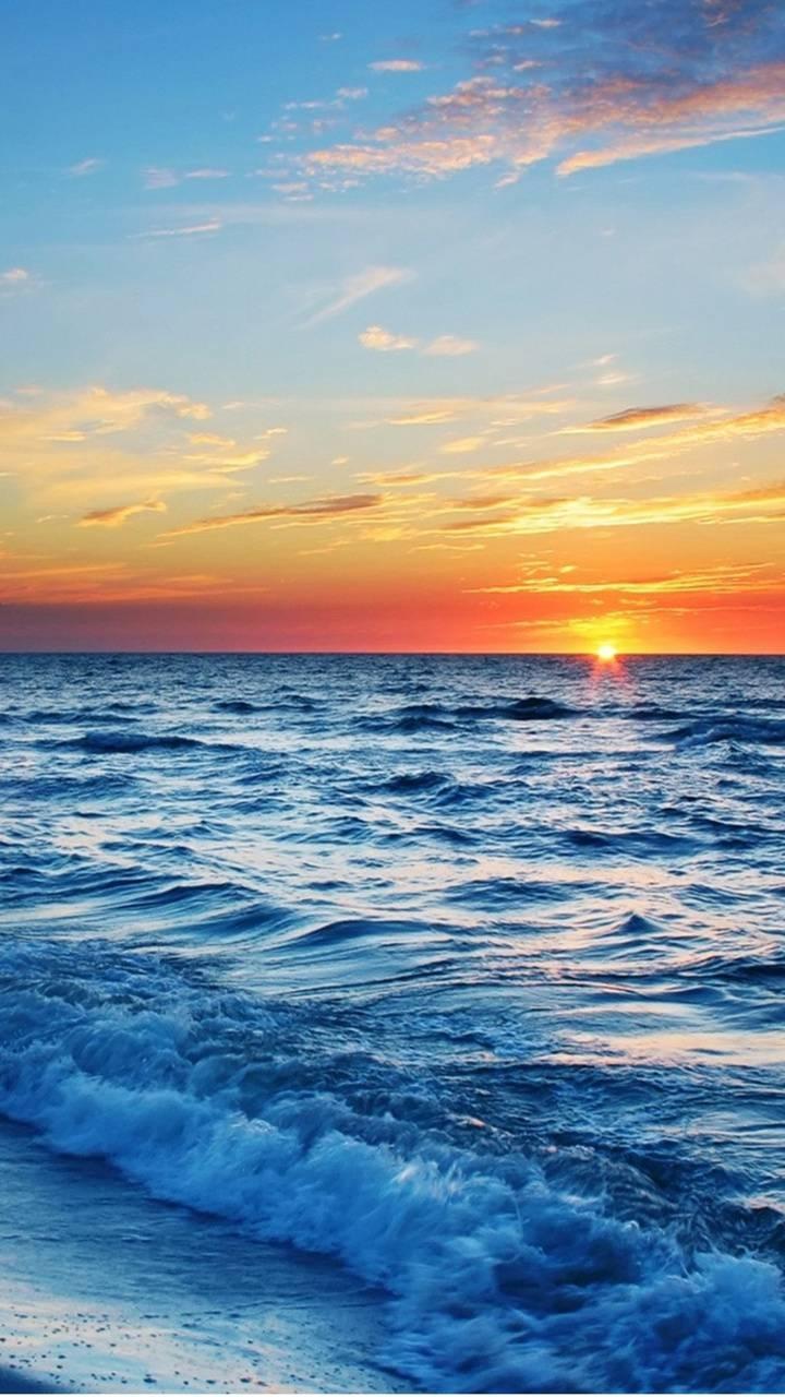 عکس زمینه غروب آفتاب اقیانوس آبی و طلایی پس زمینه