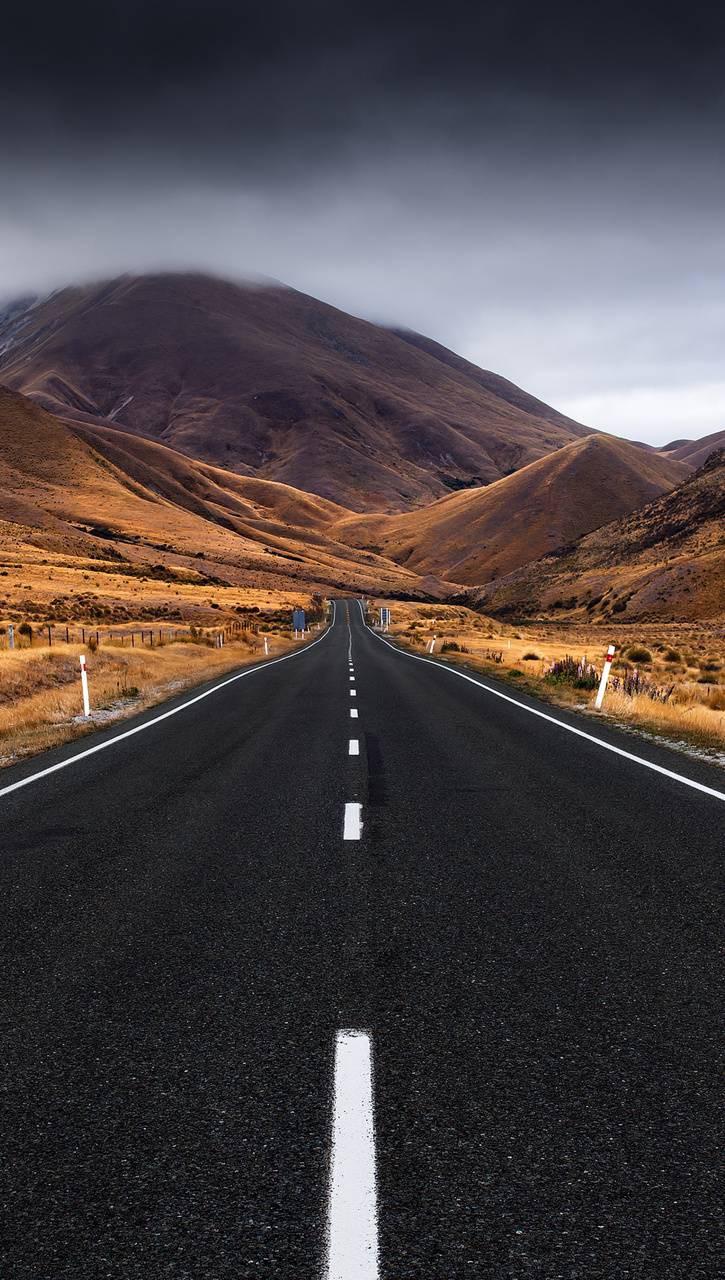 عکس زمینه جاده در کوهستان ابری پس زمینه