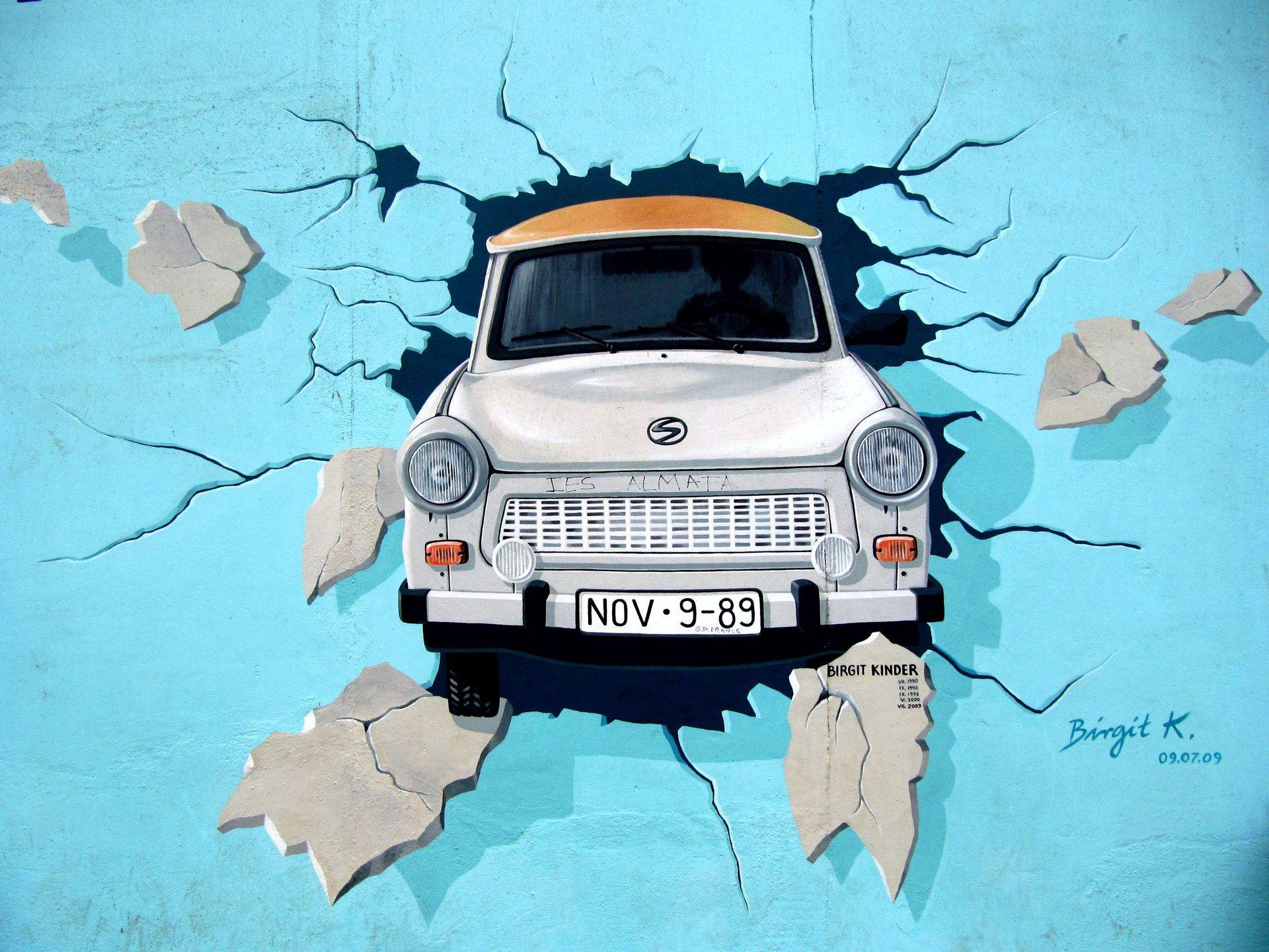 عکس زمینه نقاشی ماشین در دیوار آبی پس زمینه