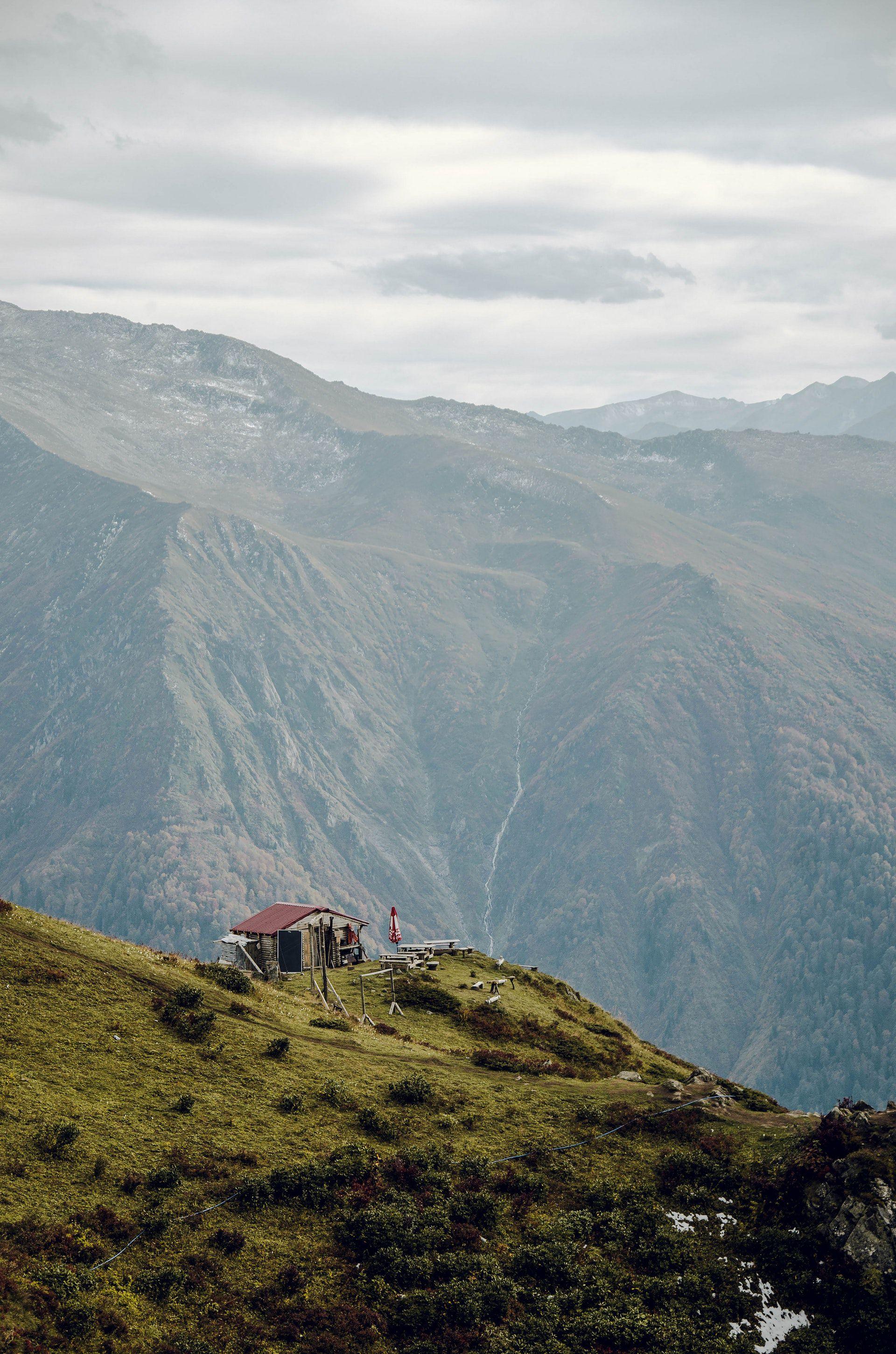 عکس زمینه کلبه روی تپه سبز پس زمینه