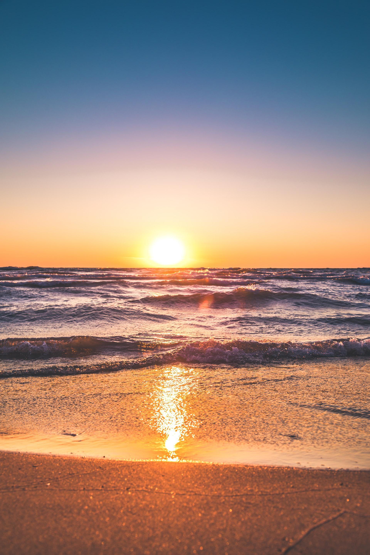 عکس زمینه منظره اقیانوس در هنگام غروب خورشید پس زمینه