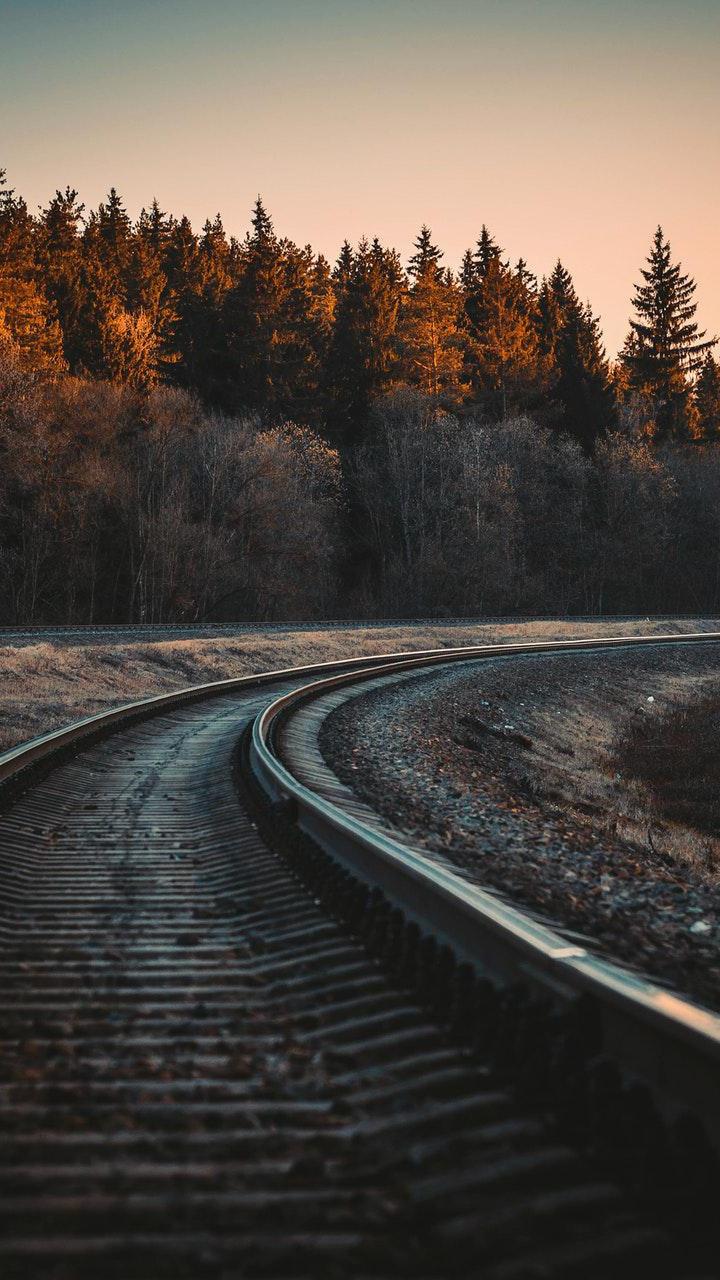 عکس زمینه قطار راه آهن درامتداد جنگل پاییزی زیبا پس زمینه