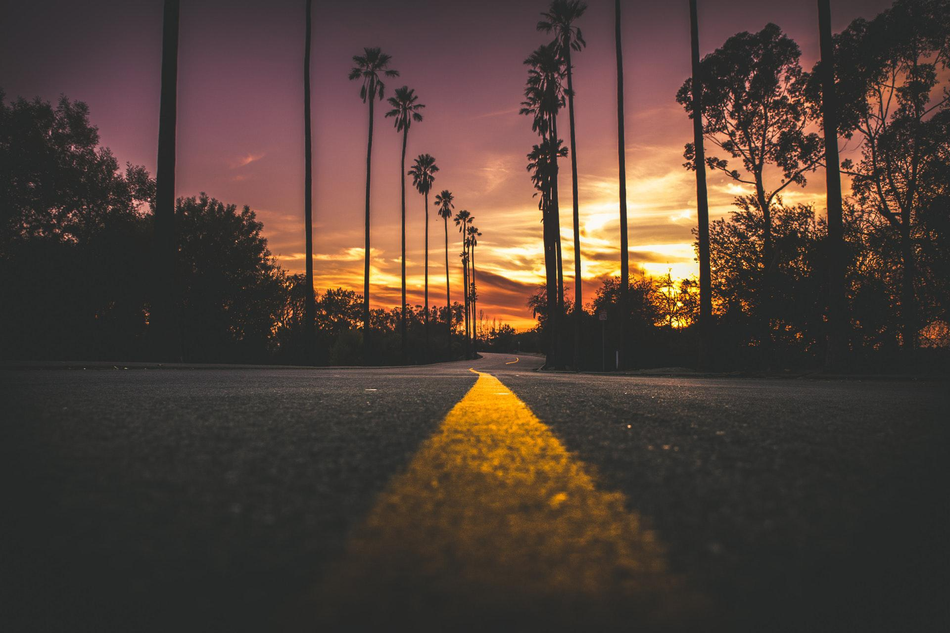 عکس زمینه جاده در شهر در هنگام غروب آفتاب پس زمینه