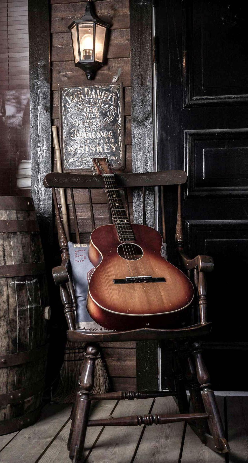 عکس زمینه گیتار چوبی کلاسیک روی صندلی قدیمی پس زمینه