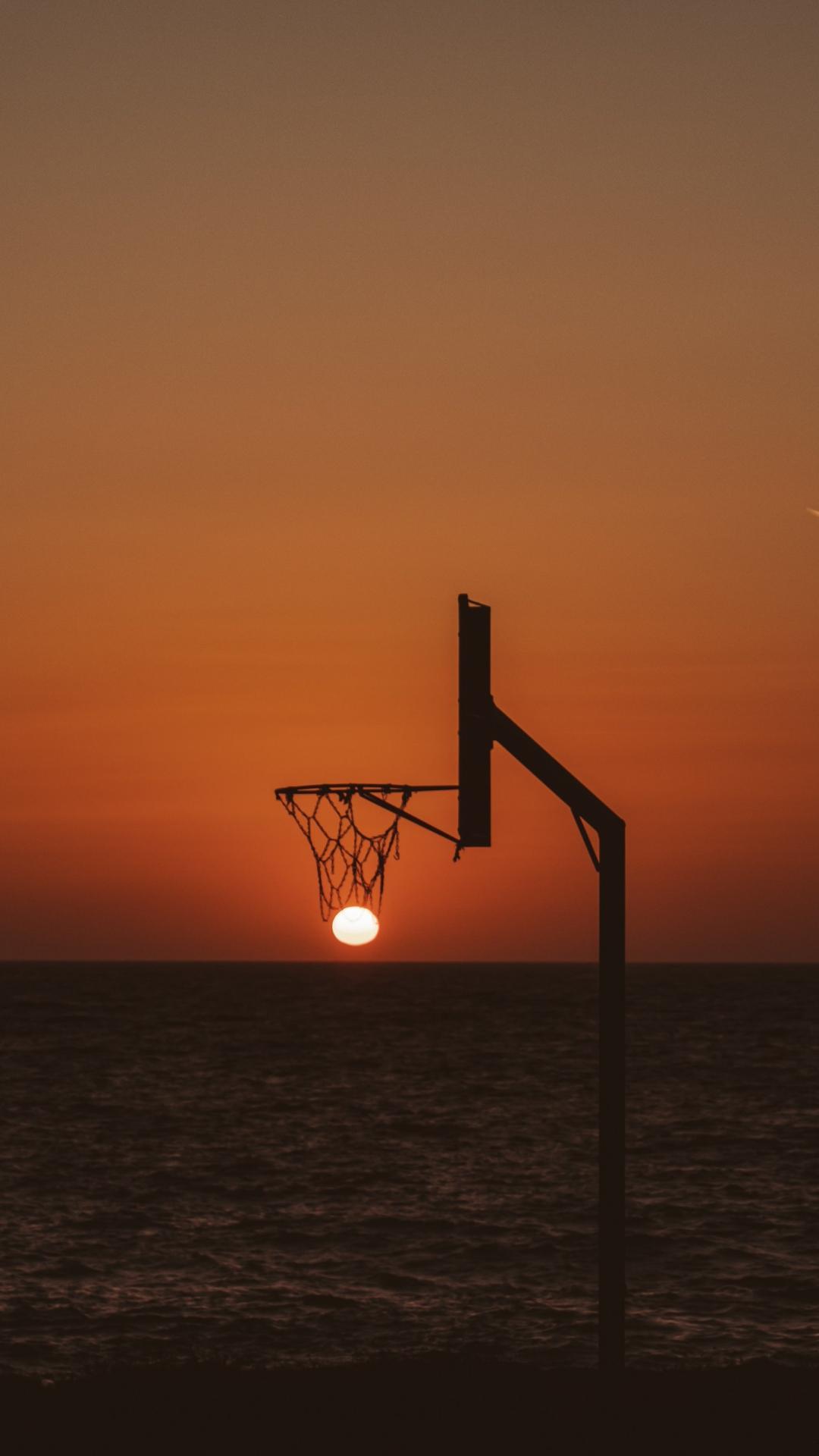 عکس زمینه غروب خورشید در سبد بسکتبال پس زمینه