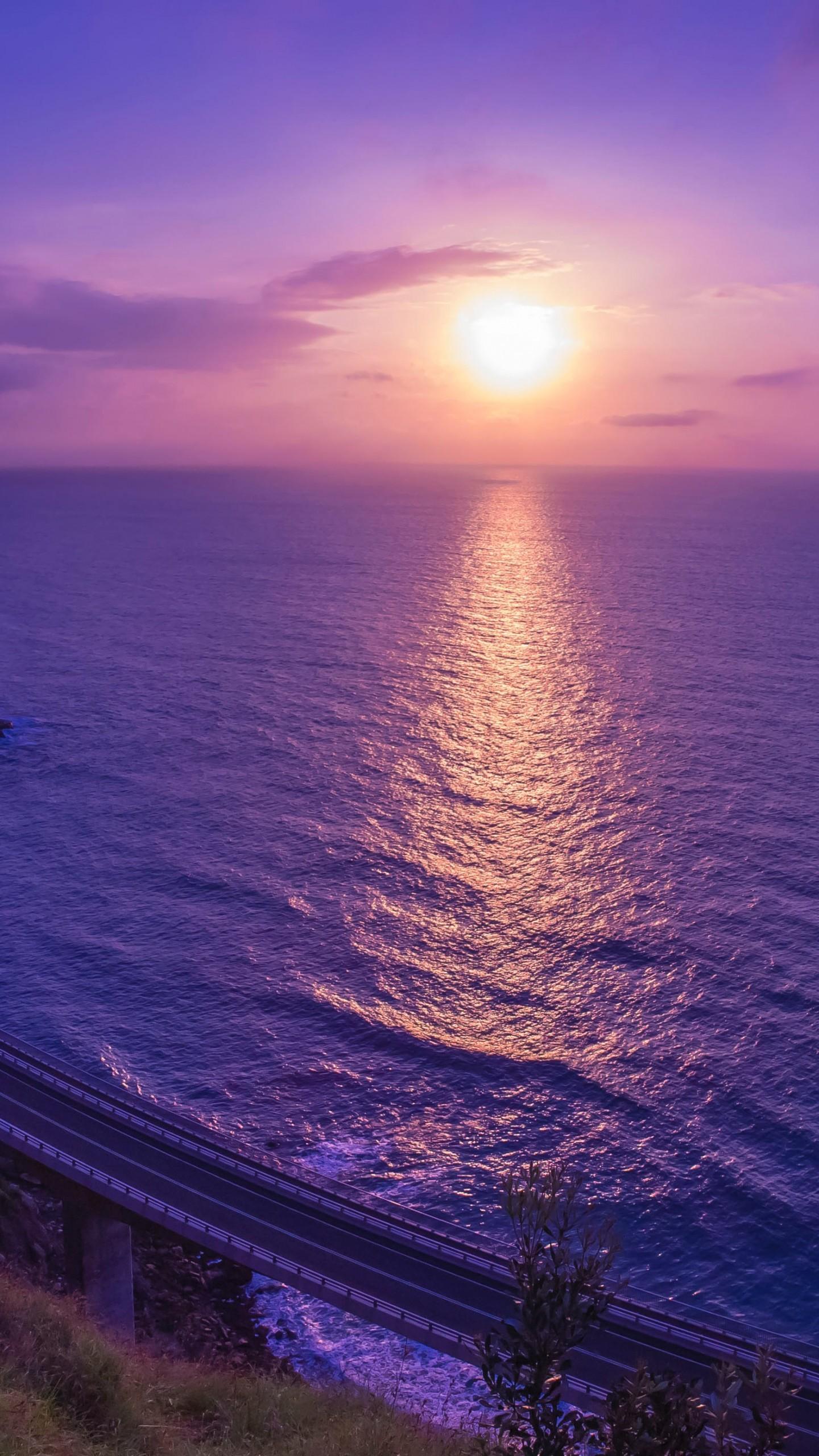 عکس زمینه غروب خورشید آسمان در دریای بنفش رنگ پس زمینه