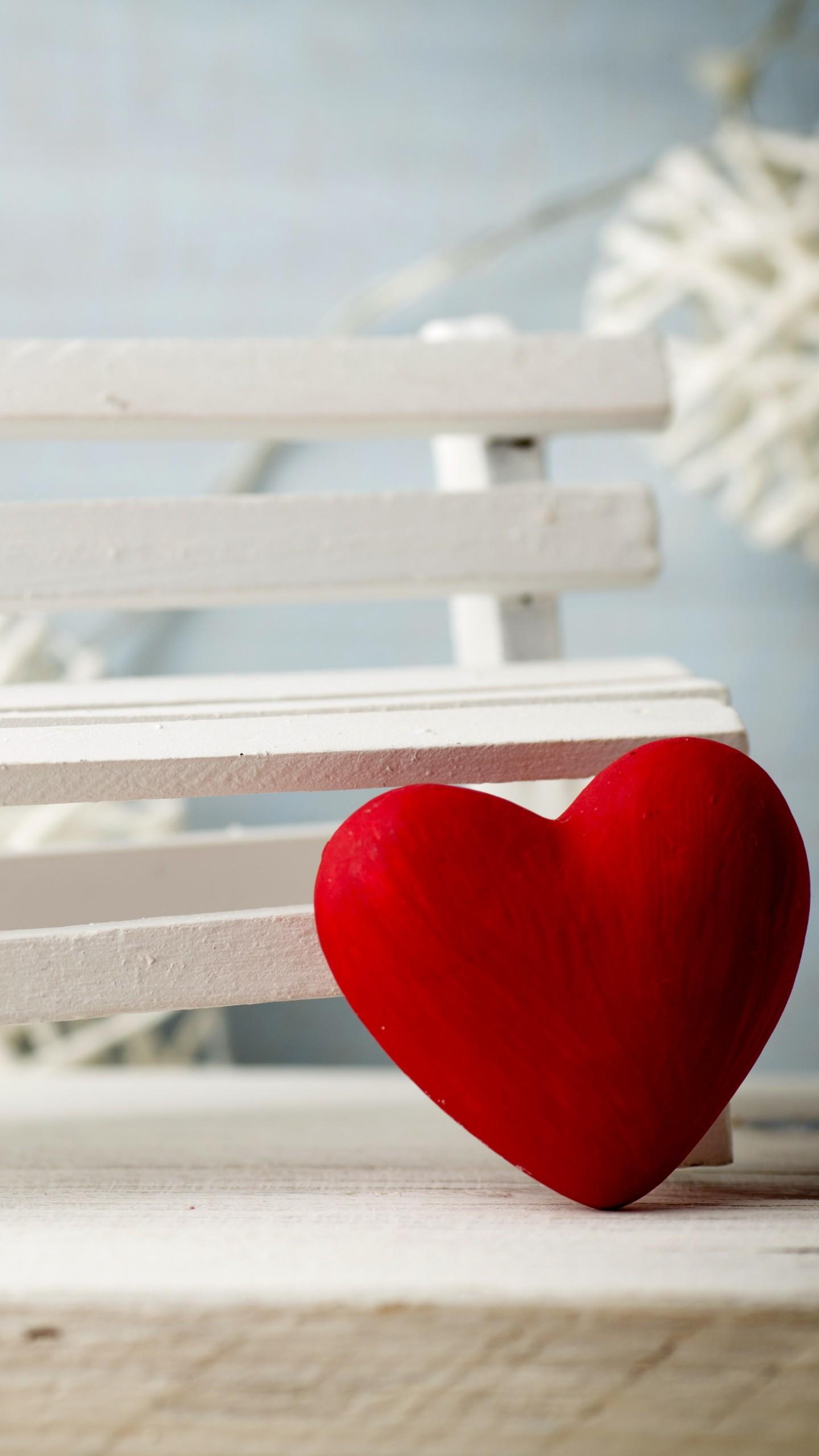 عکس زمینه قلب قرمز در کنار نیمکت سفید پس زمینه