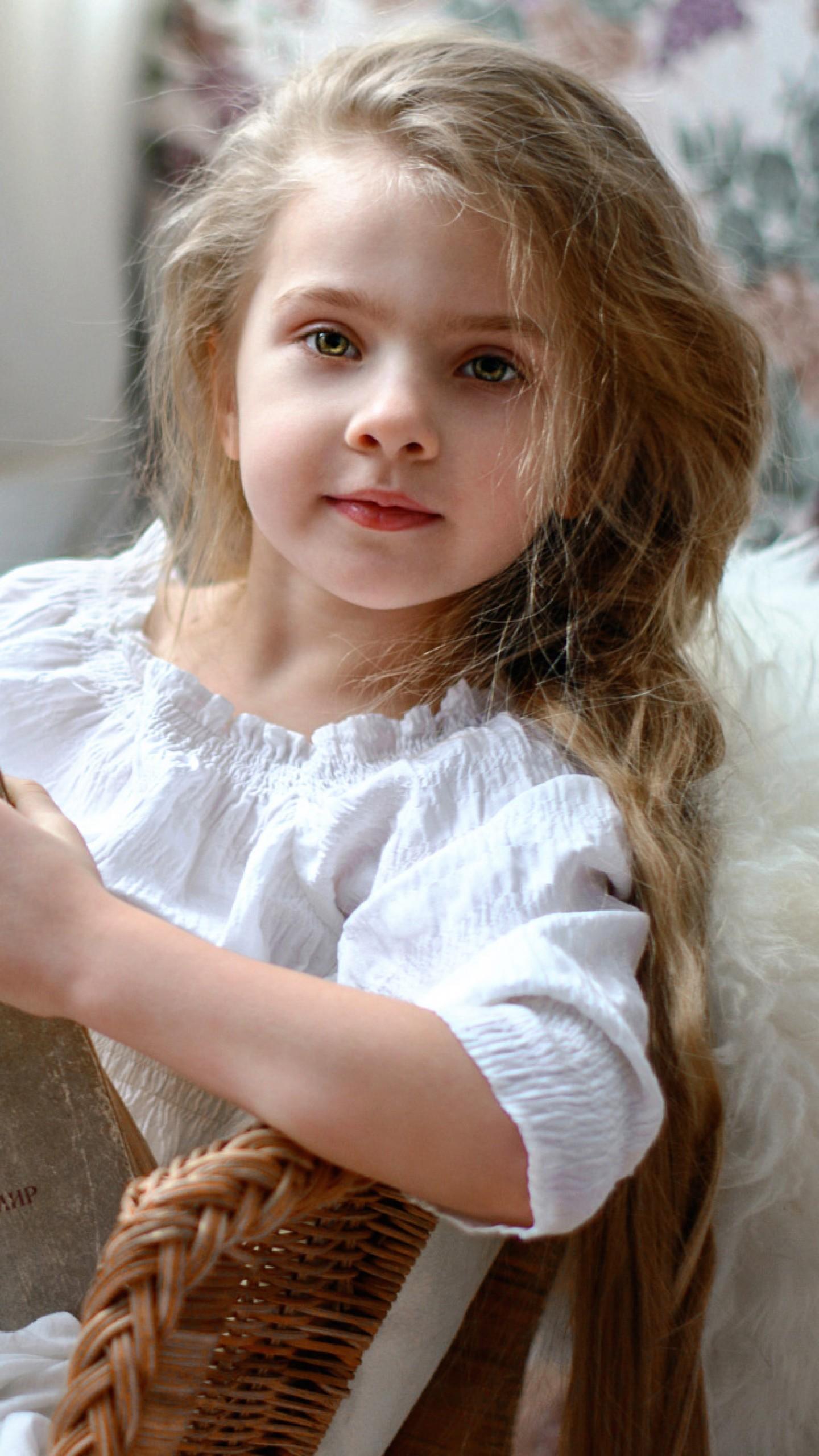عکس زمینه دختر بچه با چشمان زیبا در حال کتاب خواندن پس زمینه
