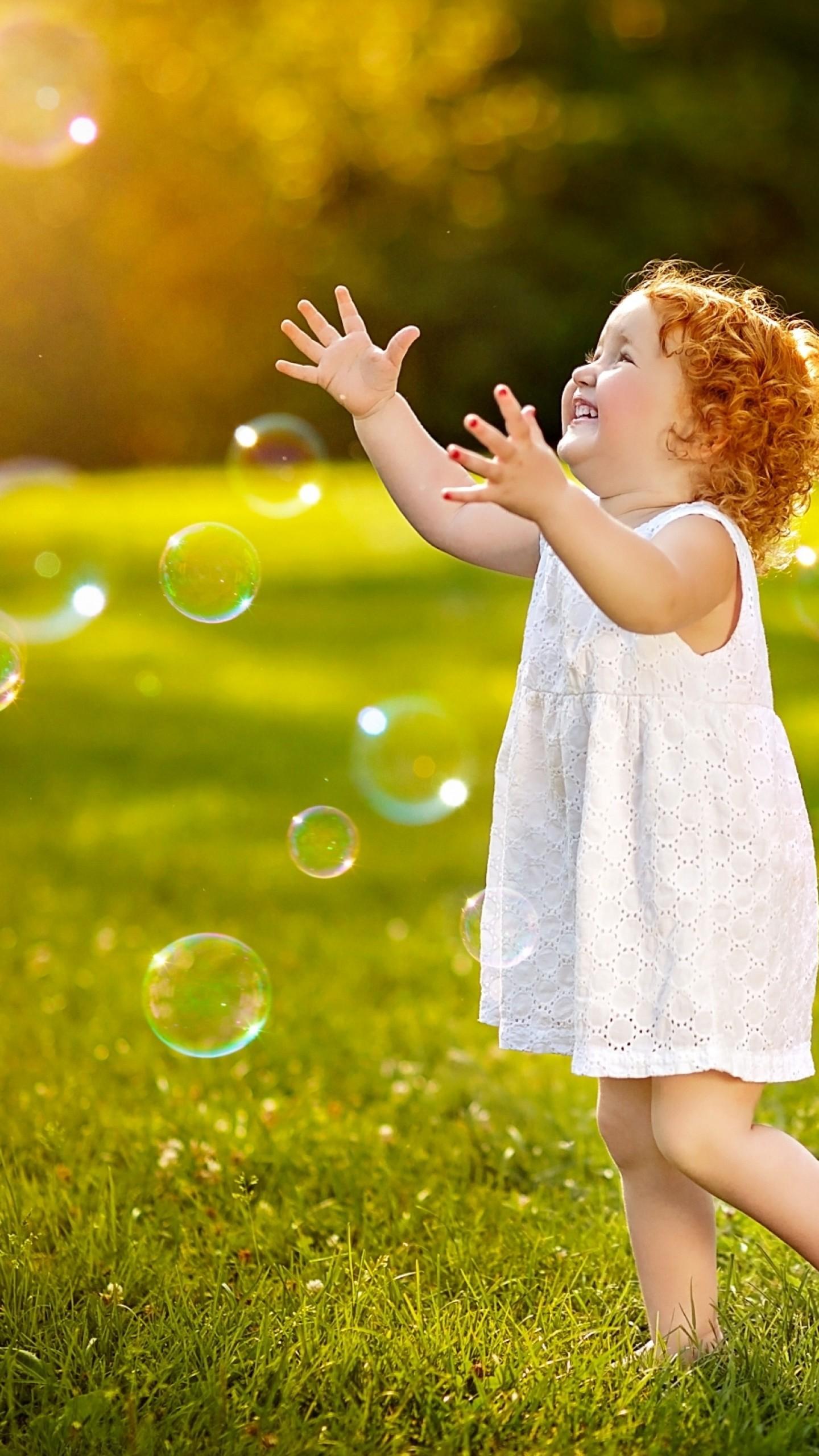 عکس زمینه دختربچه ناز در حال بازی با حباب پس زمینه