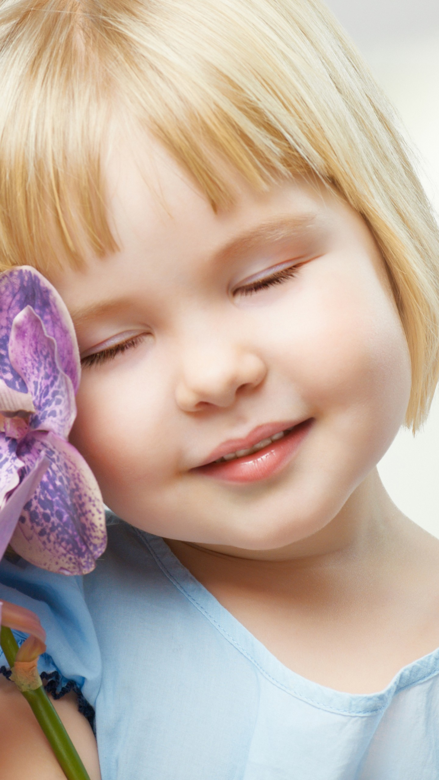 عکس زمینه دختر بچه ناز با گل های ارکیده بنفش پس زمینه