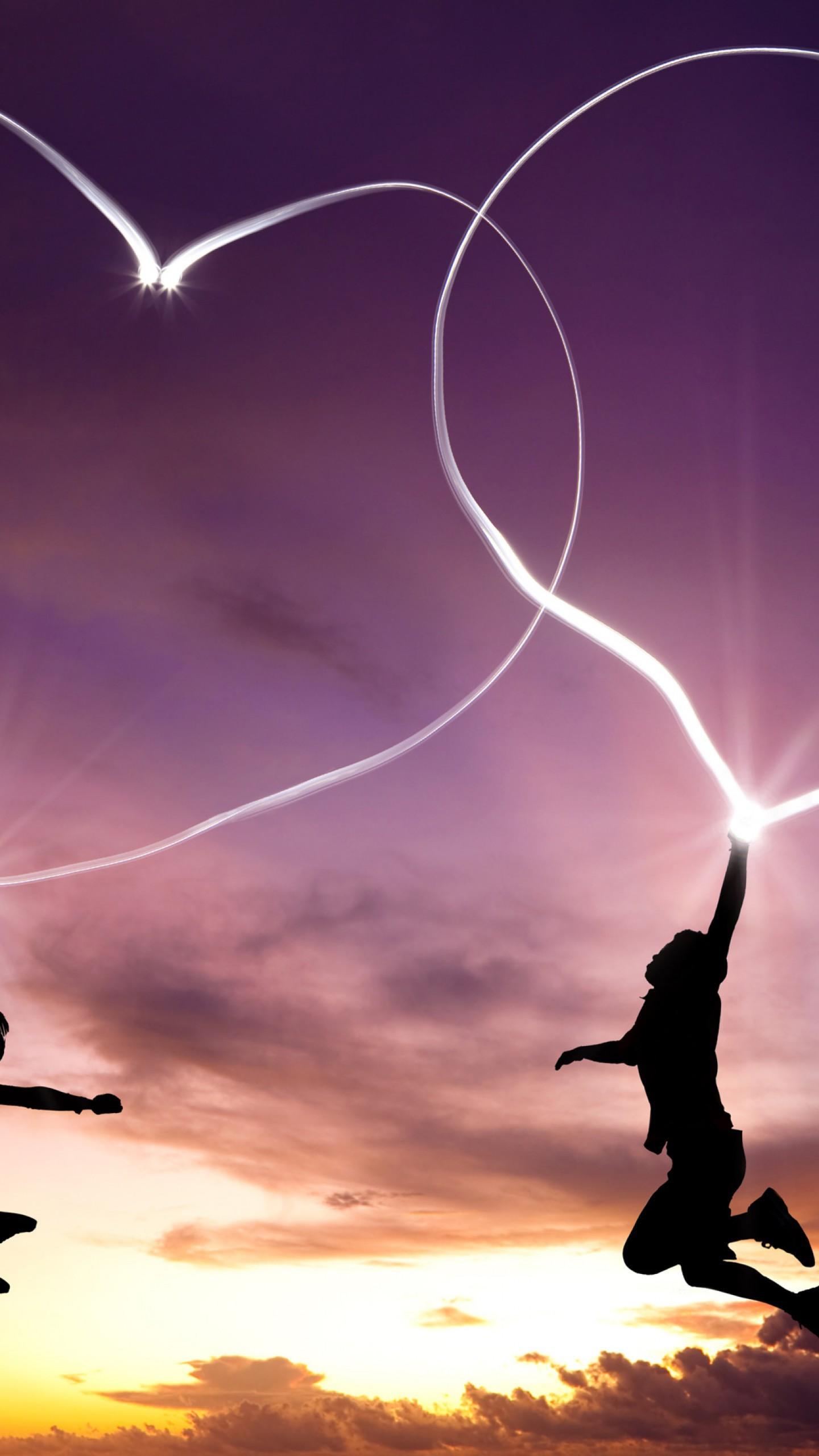 عکس زمینه کشیدن قلب های نورانی در آسمان توسط پسر و دختر پس زمینه