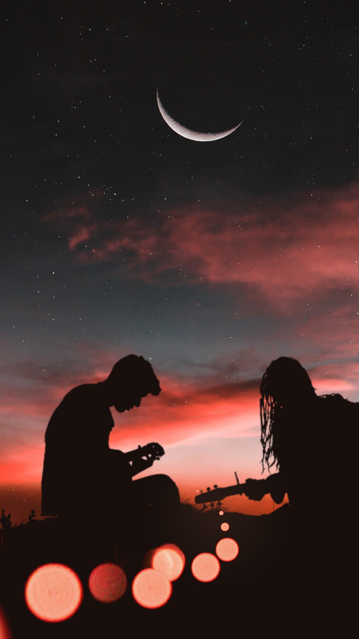 عکس زمینه پسر و دختر در حال نواختن گیتار در شب پس زمینه