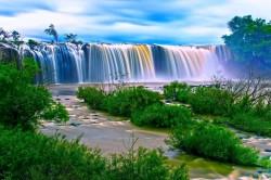 عکس زمینه آبشار آب اطراف چمن سبز در روز