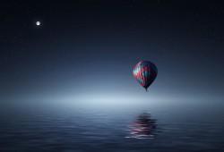 عکس زمینه بالون شناور در هوا روی آب در شب