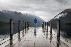 عکس زمینه فرد ایستاده در اسکله چوبی