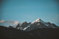 عکس زمینه برف روی قله کوه زیر آسمان پاک