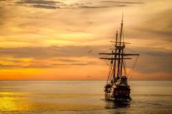 عکس زمینه قایق در غروب دریا