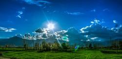 عکس زمینه آسمان نیمه ابری و دشت سر سبز
