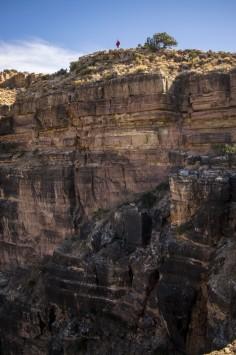 عکس زمینه مرد ایستاده در صخره