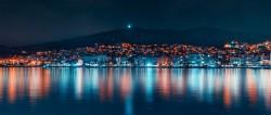 عکس زمینه ساختمان های شهر در نزدیکی آب در شب