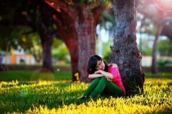 عکس زمینه دختر نشسته در کنار درخت