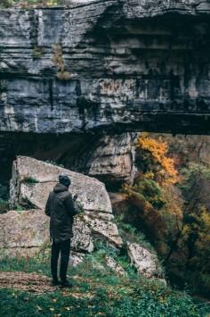 عکس زمینه مرد ایستاده کنار سخره سنگی